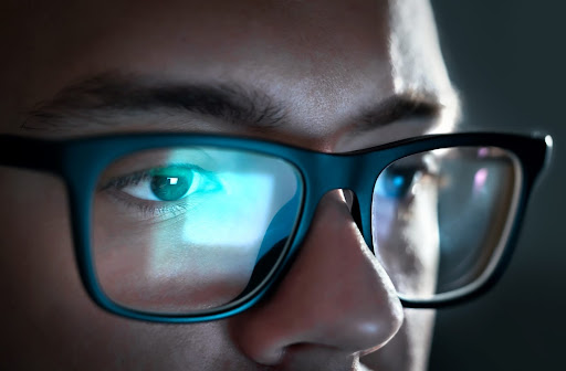 A close up of a man's glasses showing a reflection from a computer screen