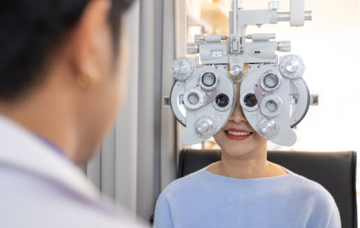 An optometrist performing a refraction test on a female patient to look for astigmatism