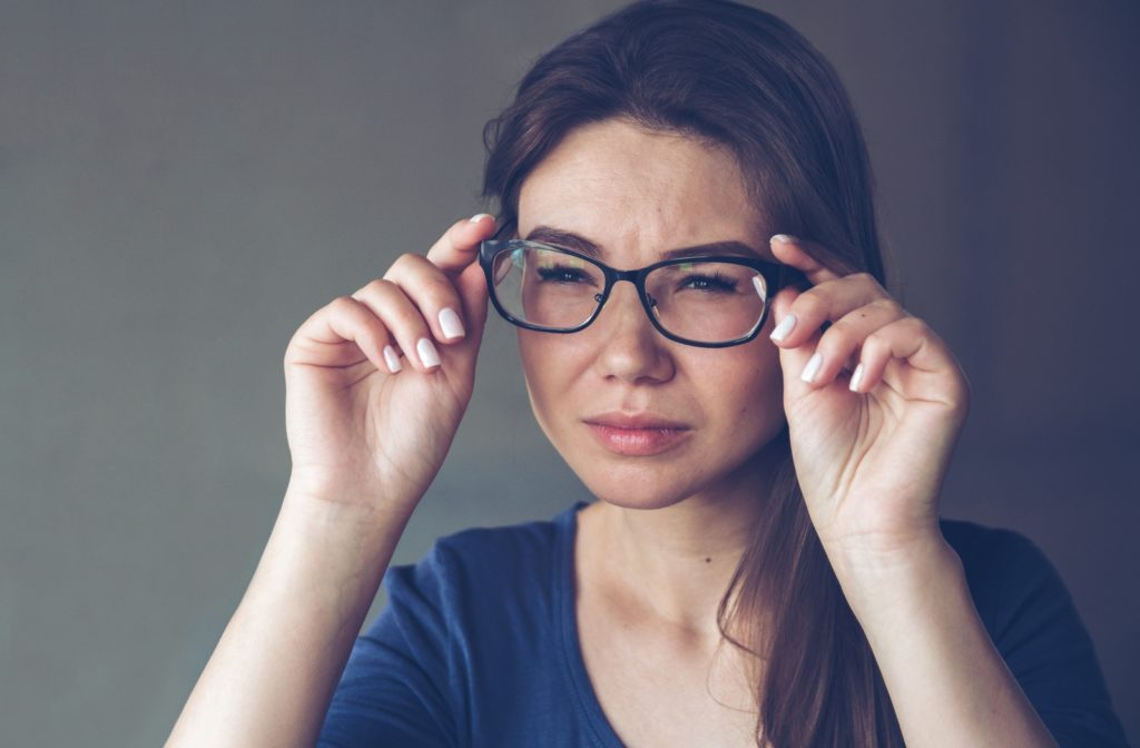 A woman with eyesight problems sees poorly through glasses because of astigmatism